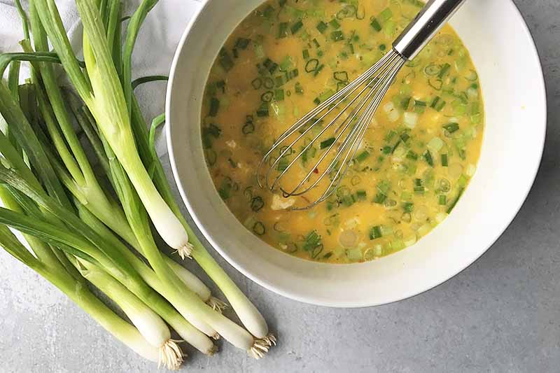 Horizontal image of a big white bowl with a yellow mixture with chopped green onions and a whisk.