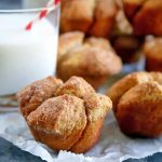 Horizontal image of golden brown monkey bread muffins on a piece of parchment paper with a glass of milk, with a striped red and white straw stuck into the beverage, on a blue-gray surface.