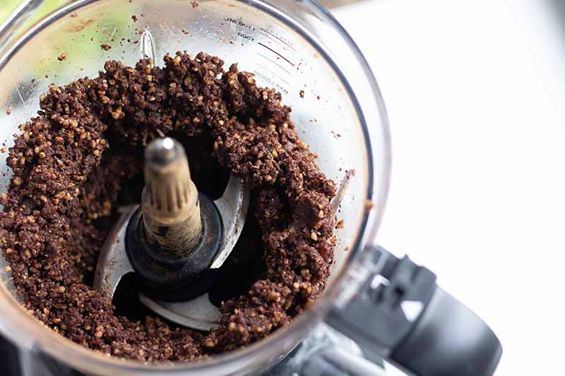 Horizontal image of a food processor with a gritty dark brown mixture.