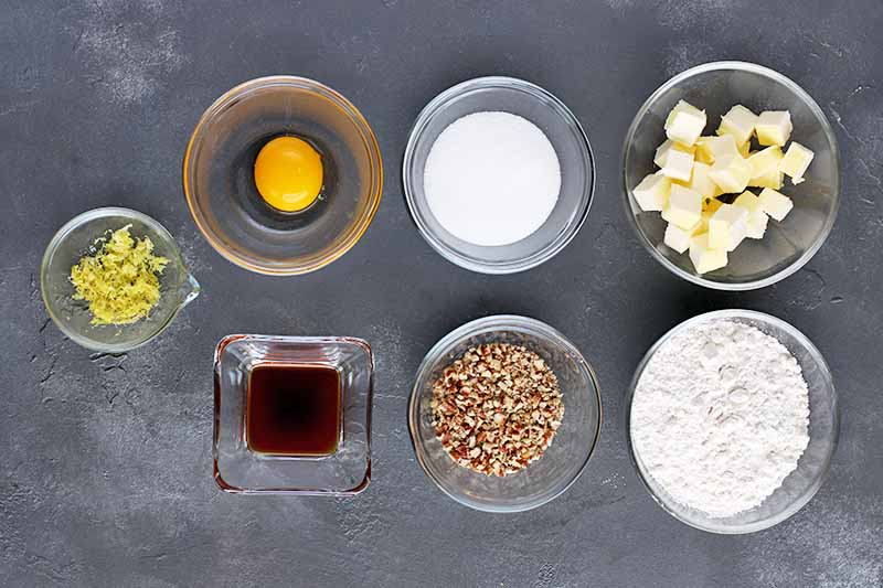 Horizontal overhead image of one small square and six small round bowls of lemon zest, egg, sugar, cubed butter, flour, chopped pecans, and vanilla extract, arranged on a gray surface.