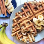 Horizontal image of two golden-brown waffles with bananas on a gray plate, next to a plate of assorted spices.