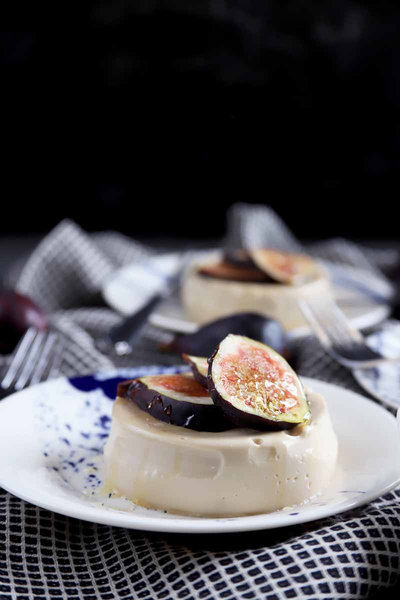 Horizontal image of two plates with circular cream desserts topped with figs in front of a black background.