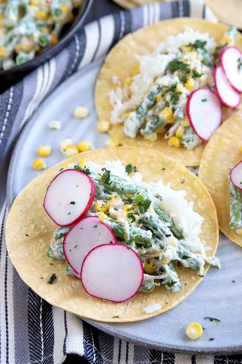 Vertical oblique overhead image of a plate full of corn and green bean tacos with cilantro crema, in yellow corn tortillas and garnished with radish slices, on a gray ceramic plate, on top of a folded gray and white striped cloth, with more of the filling mixture in a large frying pan at the top left of the frame.