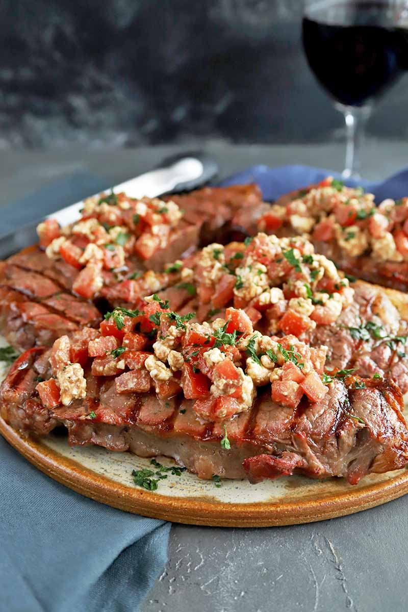 Vertical image of a tan and beige serving platter of grilled steak topped with chopped tomato, feta, and herbs, on a gray surface with a blue cloth napkin, and a glass of red wine in the background, against a mottled dark gray backdrop.