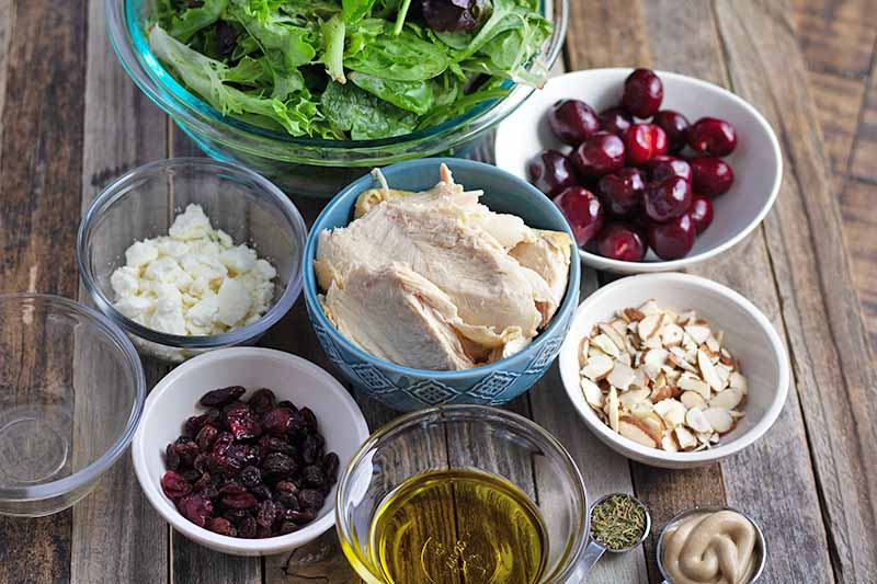 Horizontal oblique overhead image of eight small bowls of salad greens, sliced cooked chicken breast, fresh cherries, crumbled goat cheese, dried fruit, olive oil. and slivered almonds, a measuring spoon of seasonings, and another spoon of Dijon mustard, on an unfinished wood surface.