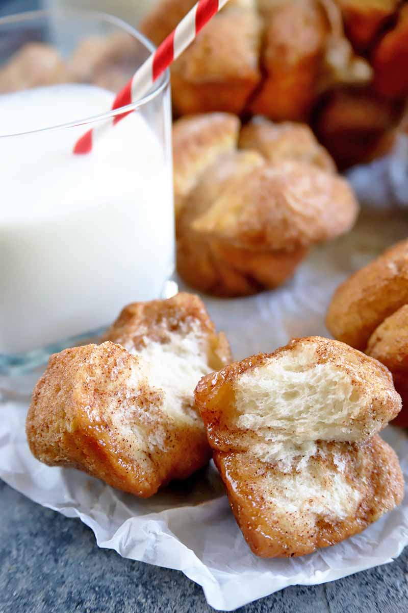 Vertical image of a monkey bread muffin in the foreground that has been torn in half to show the inside, with more in the background in soft focus next to a glass of milk with a white and red striped straw, on a piece of parchment paper on top of a blue-gray surface.