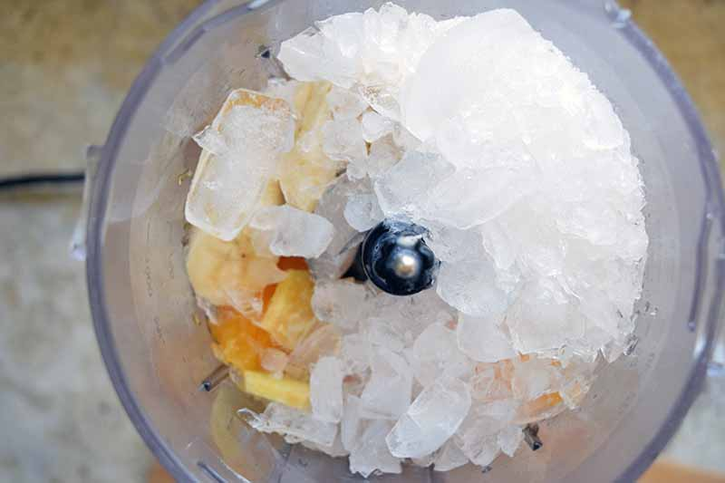 Overhead horizontal image of crushed ice and fruit in the clear plastic canister of a blender, on a gray kitchen countertop.