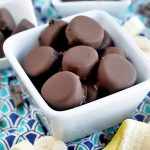 Horizontal image of one medium-sized and two smaller white ceramic dishes of chocolate-covered banana slices, surrounded by more whole and cut fruit and candy chunks on a dark and light blue patterned cloth.