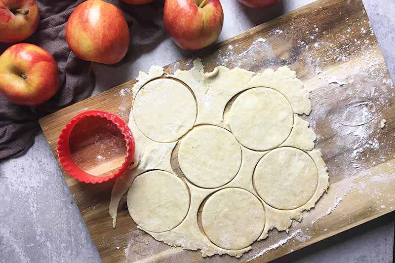 Horizontal image of a wooden cutting board with a dough cut out in circles surrounded by red pommes.