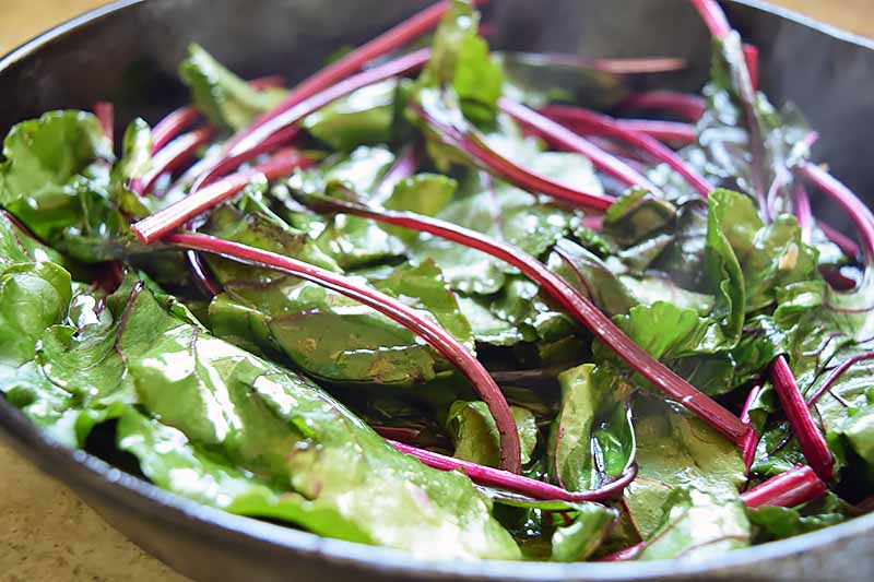Horizontal image of slightly wilted greens in a cast iron skillet.