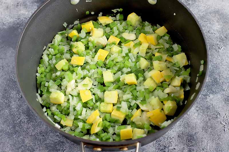 Horizontal image of a mixture of yellow, green, and white chopped vegetables in a black pot.