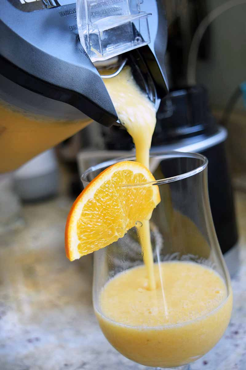 Vertical image of a homemade smoothie being poured from a clear and black plastic pitcher into a glass, garnished with a slice of fresh fruit, on a gray kitchen countertop.