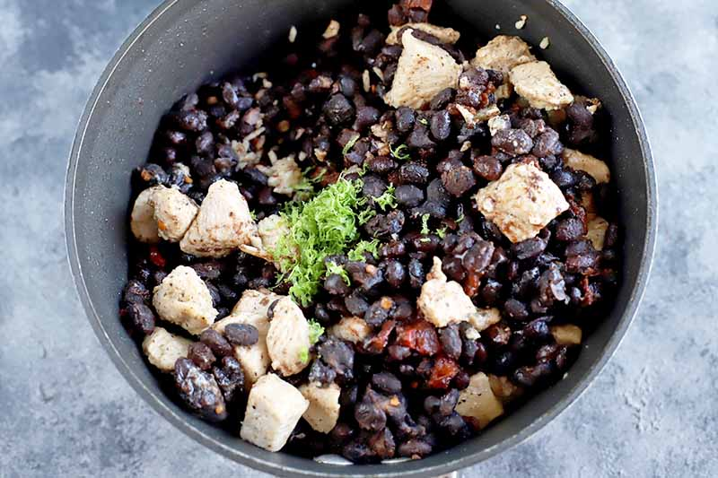 Horizontal overhead image of a stainless steel bowl of black beans, cooked bite-sized pieces of chicken breast, lime zest, and red canned chipotle peppers, on a gray and white surface.