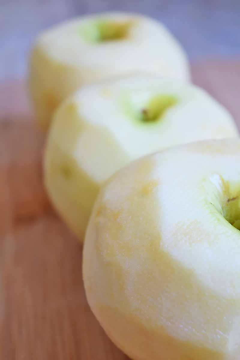 Vertical image of three peeled whole apples on a wooden board.