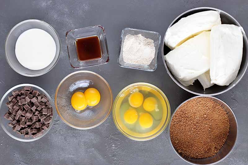 Horizontal image of a collection of square and round glass and metal bowls of heavy cream, vanilla extract, flour, cream cheese, unrefined sugar, eggs and egg yolks, and dark chocolate chips, on a gray surface.
