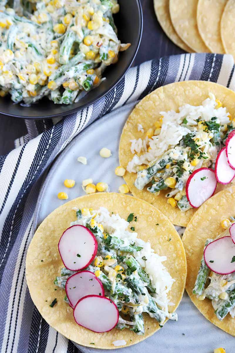 Overhead image of three vegetarian tacos garnished with thinly sliced radish on a gray plate on top of a gray and white striped cloth, with a fanned out stack of yellow corn tortillas at the top right and a large nonstick frying pan of corn and green bean filling at the top left of the frame.