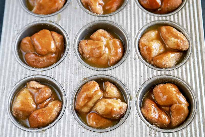 Overhead horizontal image of bite-sized piece of biscuit dough topped with cinnamon, sugar, and melted butter, in a metal muffin tin.