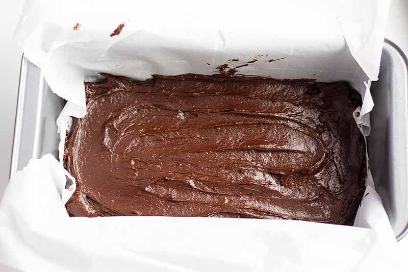 Horizontal image of a pan lined with parchment paper with a dessert topped with chocolate frosting.