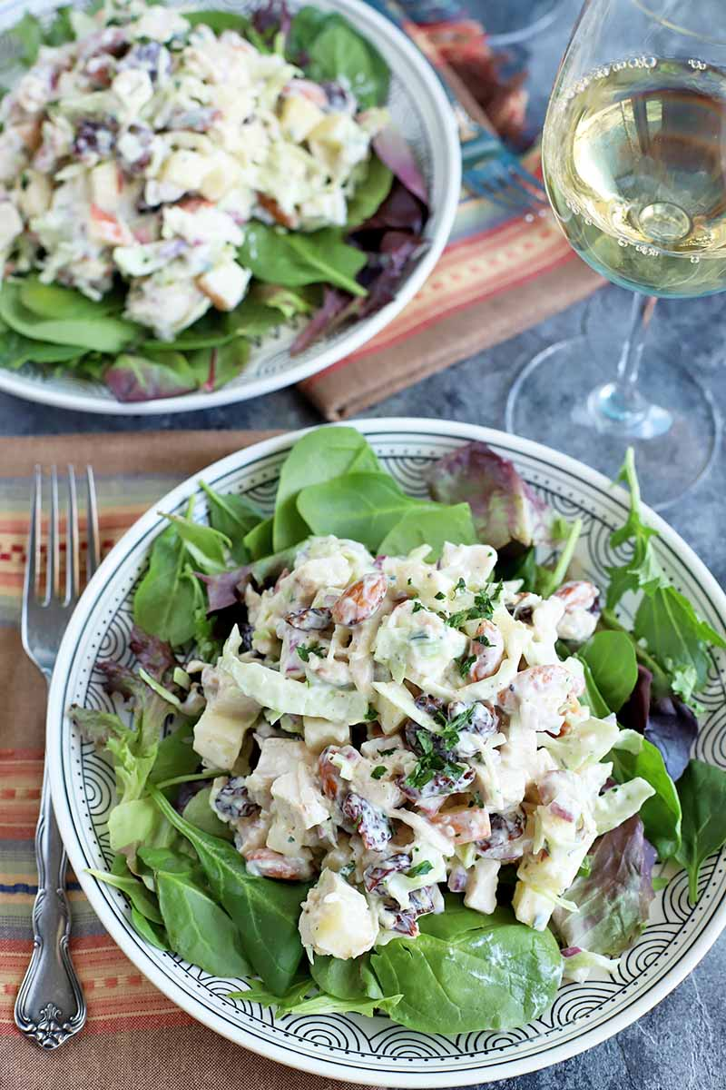 Overhead image of two white plates of chicken salad with fresh and dried fruit and nuts on a bed of mixed greens, with folded striped multicolored cloth napkins, a fork, and a glass of white wine, on a gray surface.