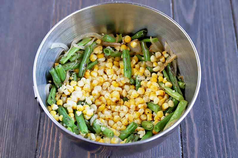 Horizontal overhead image of a stainless steel bowl of trimmed green beans and yellow corn kernels, on a brown wood table.