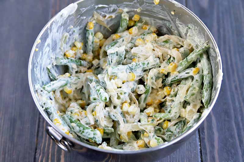 Horizontal image of a stainless steel bowl of corn and green beans coated in a white sauce, on a brown wood surface.
