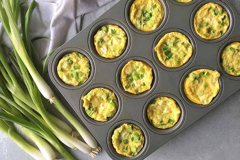 Horizontal image of a muffin pan with a baked breakfast dish with scallions.