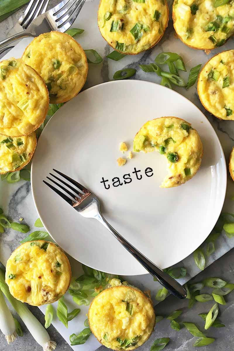 "Vertical image of a plate with ""taste"" on it, surrounded by breakfast egg bites with green vegetables and a fork."