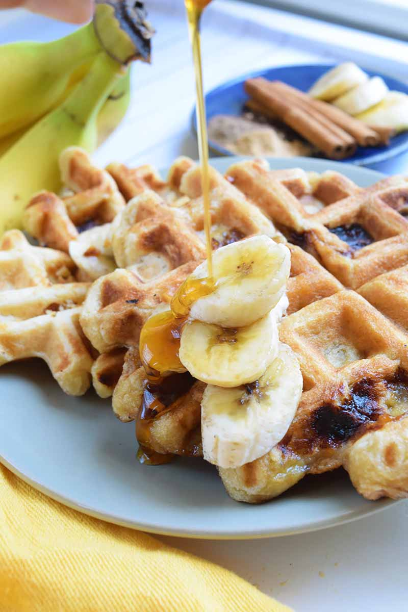 Vertical image of syrup being poured over thick waffles with banana slices.
