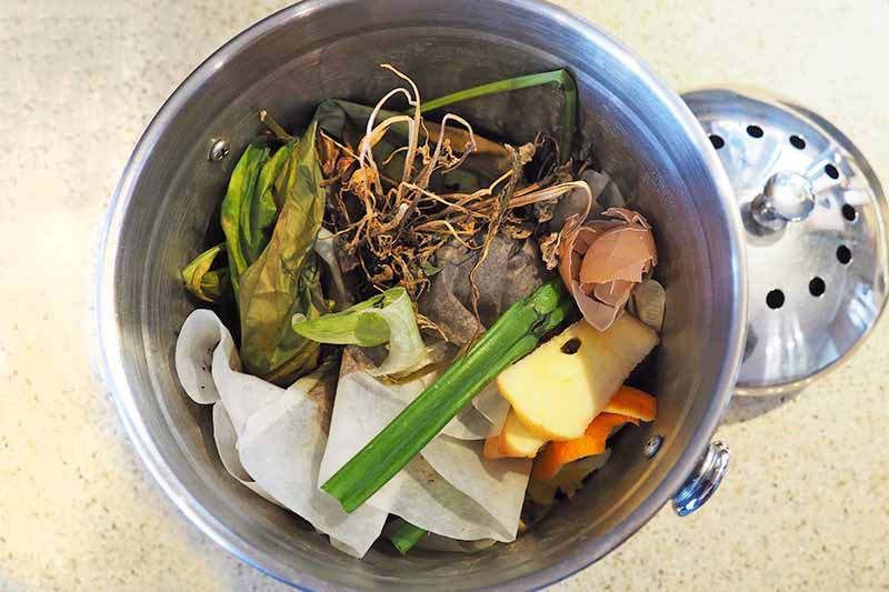 Overhead image of a metal pail filled with paper and kitchen waste including vegetable peels and scraps, with a vented metal lid to the right, on a speckled beige countertop.