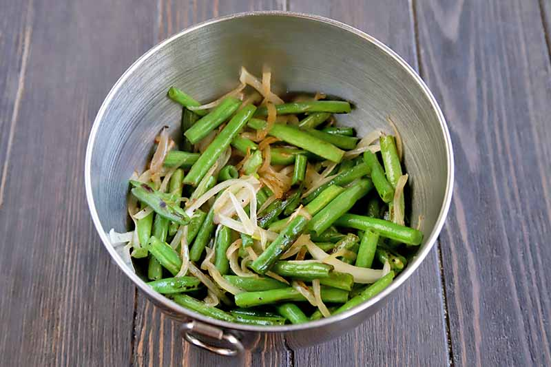 Overhead horizontal imageo of a stainless steel bowl with a ring handle, filled with cooked green beans and onions, on a brown wood surface.