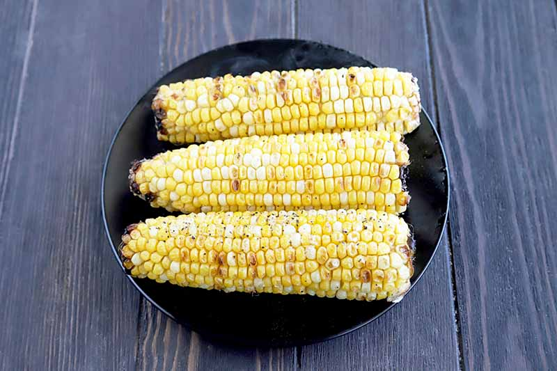 Horizontal overhead image of three ears of grilled corn on a black ceramic plate, on a brown wood surface.