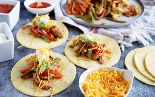 Horizontal image of a chicken and pepper mix with soft shell tacos, sauce, and shredded cheese.