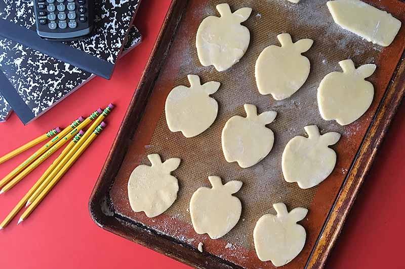 Horizontal image of apple and pencil unbaked cookie dough cut-outs on a baking sheet.