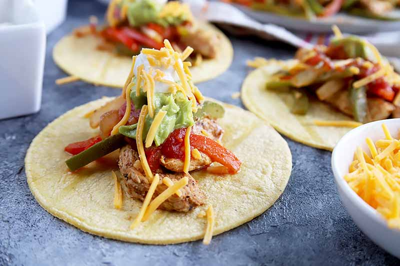 Horizontal image of three soft tacos topped with spiced chicken strips, onions, and peppers, with various condiments piled high on top.