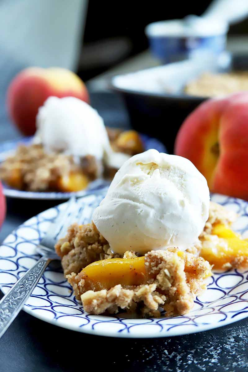 Vertical head-on image of two blue and white plates of peach crumble topped with vanilla ice cream, with a fork on the edge of the plate in the foreground, and whole stone fruit and a baking dish in soft focus in the background.