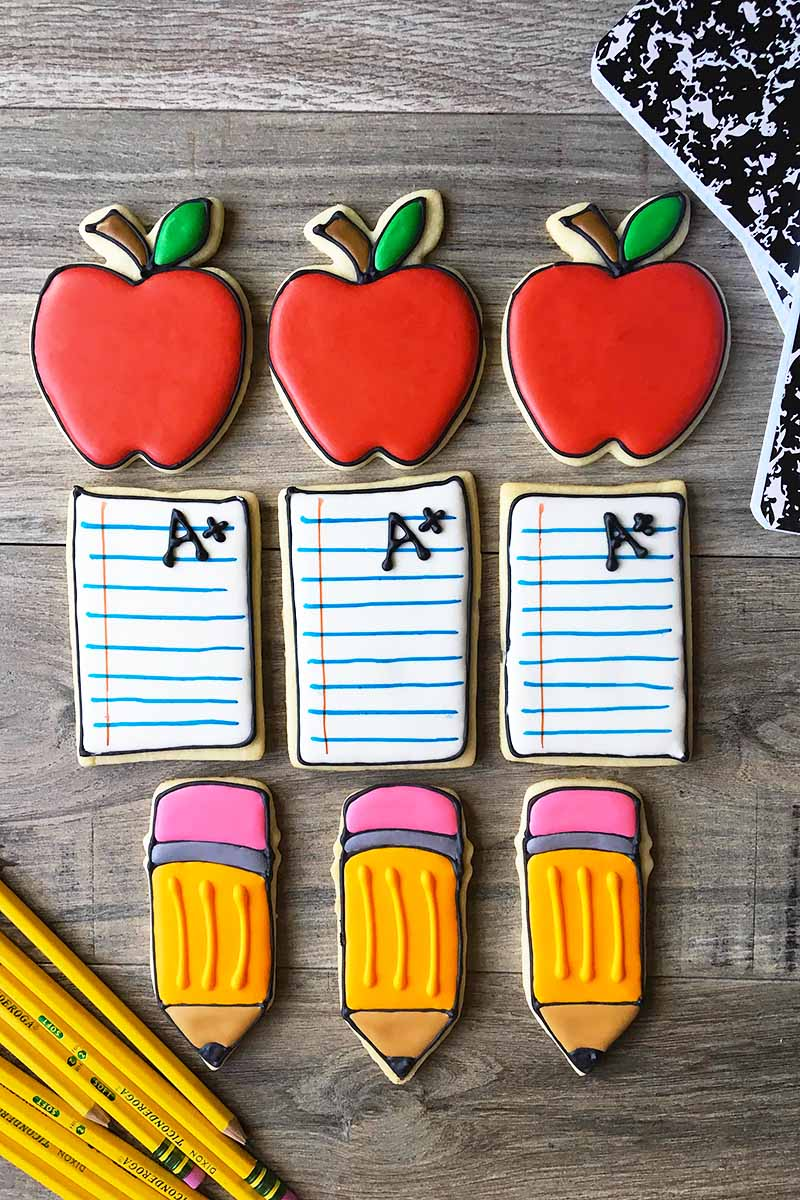 Vertical image of neat rows of three cookies each in apple, notebook paper, and pencil shapes.