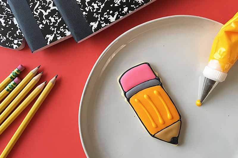 Horizontal image of a pencil dessert with piping details.
