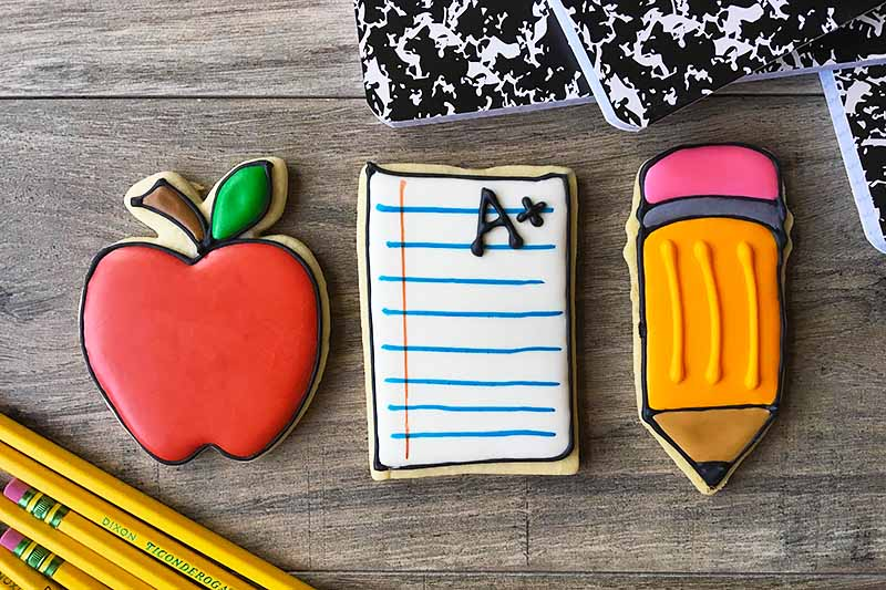 Horizontal image of a row of an apple, paper, and pencil cookie.