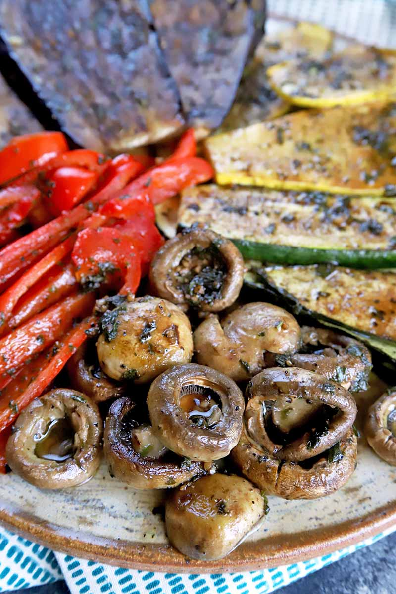 Vertical close up image of cooked mushrooms, peppers, and squash.