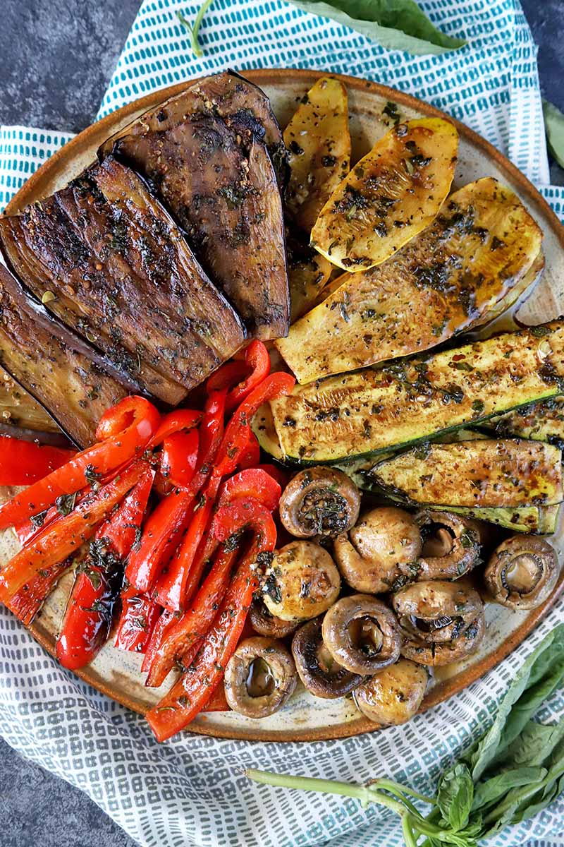 Vertical top-down image of assorted cooked veggies on a platter.