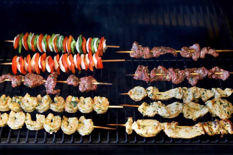 Horizontal image of wooden skewers of peppers and onions, shrimp, chicken, and steak, cooking on the grill.