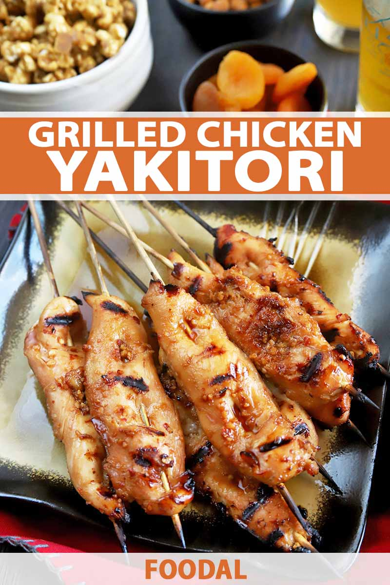 Vertical overhead image of a gold and black square plate of grilled chicken yakitori on bamboo skewers, arranged so they are all facing the same direction, on a wood table on top of a red cloth, with bowls of snack and dried fruit, and glasses of beer, printed with orange and white text near the middle and at the bottom of the frame.