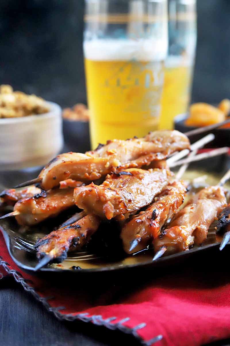 Vertical head-on image of a black and gold plate of grilled chicken skewers, on a red cloth with a blue stitched border, with two tall glasses of beer and black and white bowls of snacks in soft focus in the background, on a brown wood table.