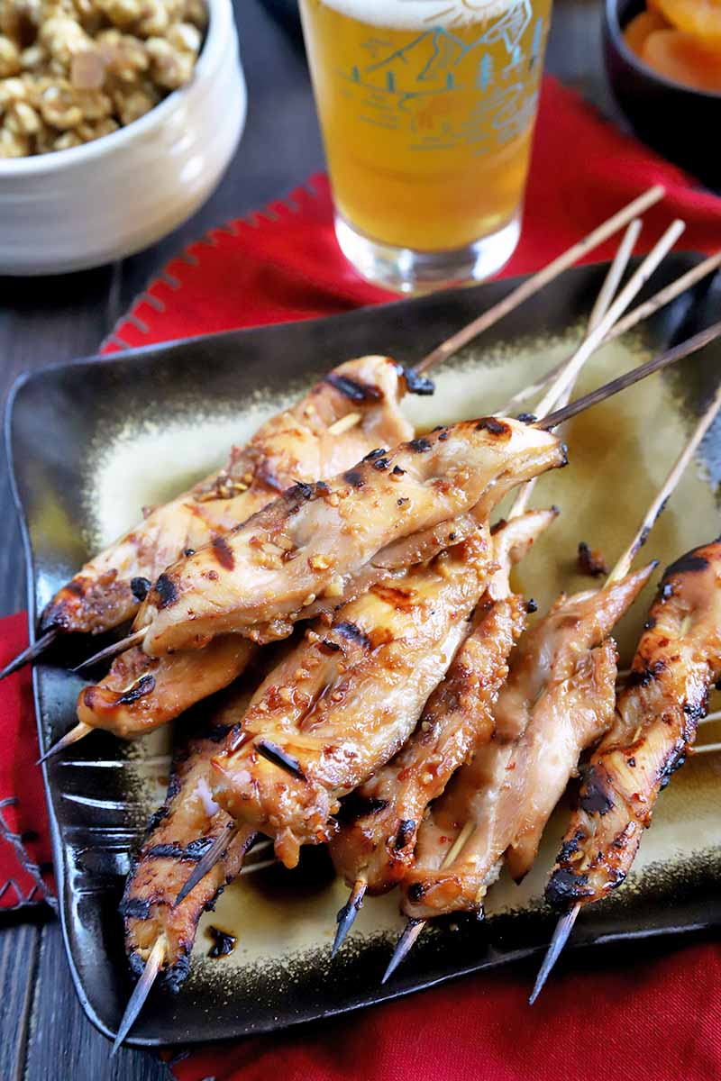 Vertical image of a square black and gold plate of grilled marinated Japanese-style chicken on bamboo skewers, on a red cloth with a glass of beer and bowls of snack foods in the background, on a wooden table.