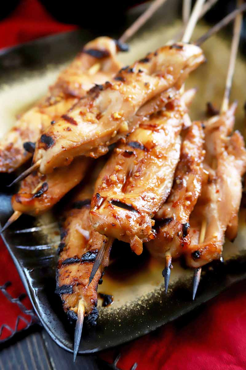 Vertical image of grilled chicken yakitori on bamboo skewers, piled on a square gold serving dish with a black border, on a red cloth on top of a dark colored wood table.