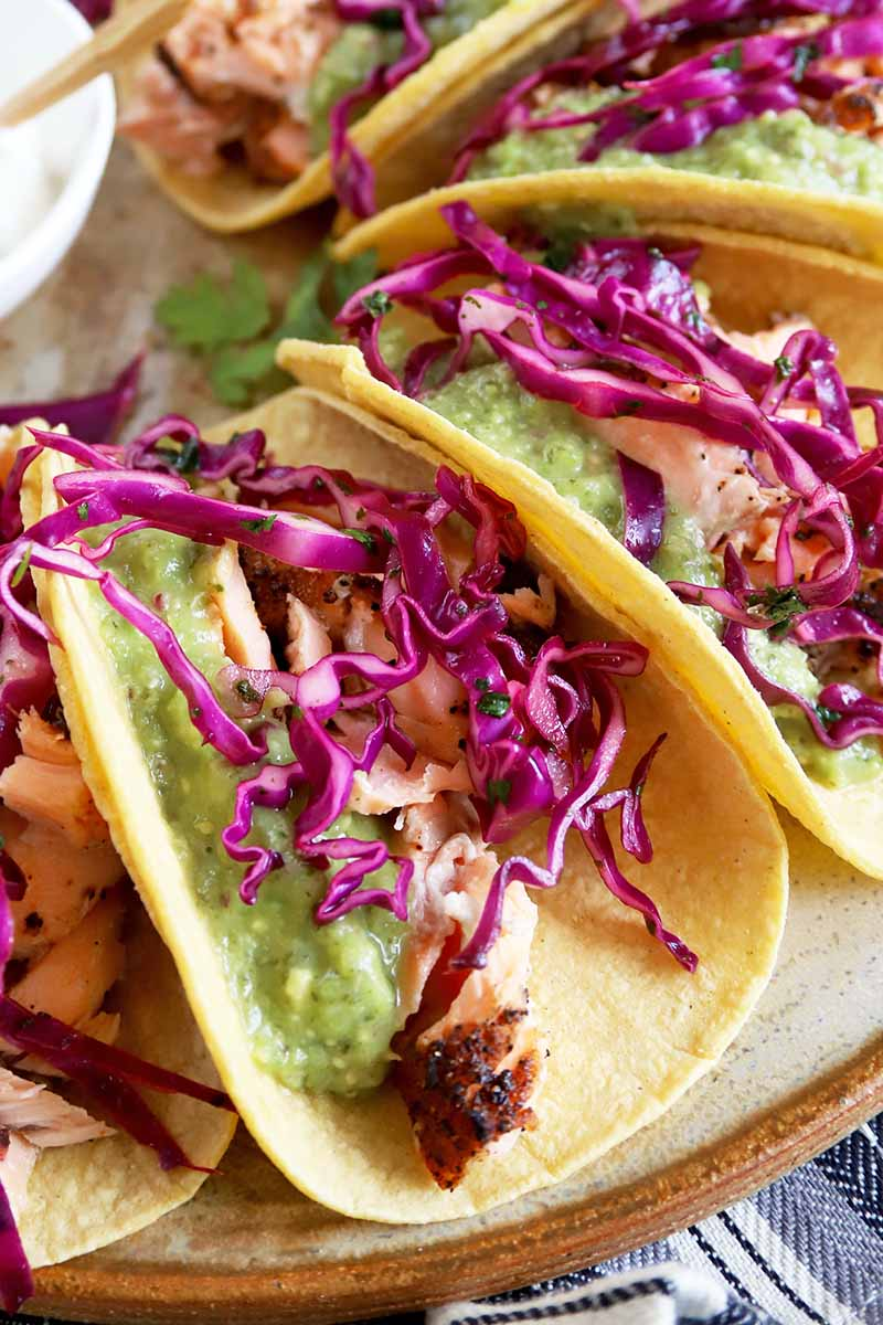 Vertical closeup image of several salmon tacos with tomatillo guacamole and red cabbage slaw in corn tortillas, on a brown and beige serving platter with a small white dish of sour cream, on a gray, white and navy blue striped cloth.