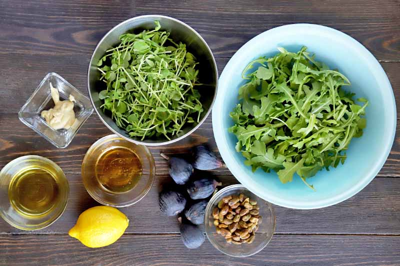 Overhead horizontal image of a small square glass bowl of Dijon mustard, three small round glass bowls of vinegar, honey, and pistachios, a medium-sized stainless steel bowl of pea shoots and a slightly larger pale blue glass bowl of arugula, a lemon, and six fresh purple figs, on a dark brown wood table.