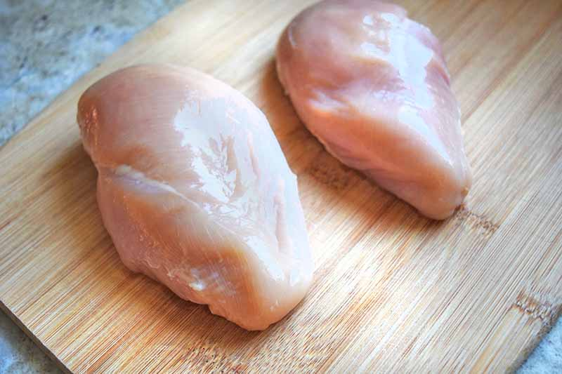 Two boneless skinless chicken breasts on a wood cutting board, on a gray kitchen countertop.