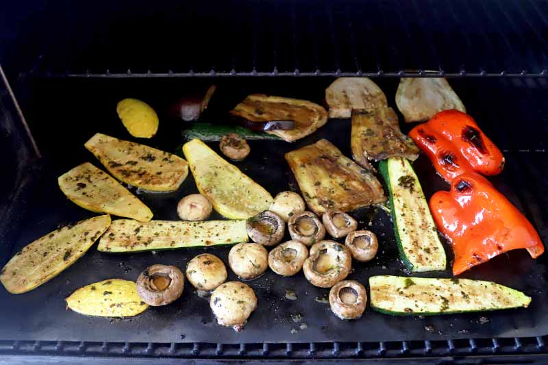 Horizontal image of a variety of veggies on a grill.
