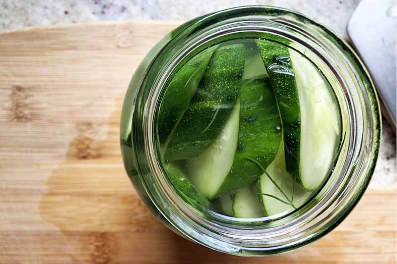 Horizontal overhead image of a jar of sliced cucumbers in brine to the right, on a wooden cutting board on a speckled kitchen countertop.